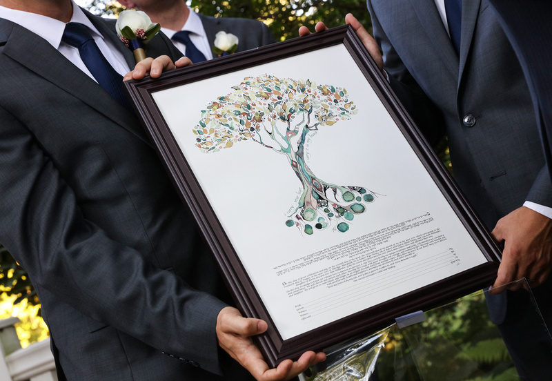 Wedding photography, three groomsmen hold the ketubah, a beautiful watercolor tree.