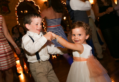 Candid image of the young ring-bearer and flower girl dancing and laughing during reception. 5 reasons you need to click with your wedding photographer.