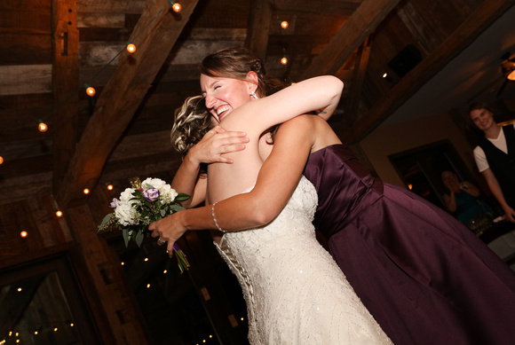Wedding photography, the bride hugs the catcher of the bouquet, who is smiling.