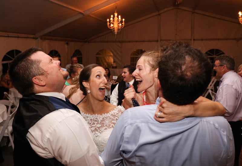 Wedding photography, a bride and groom dance closely with another couple. They are all laughing.