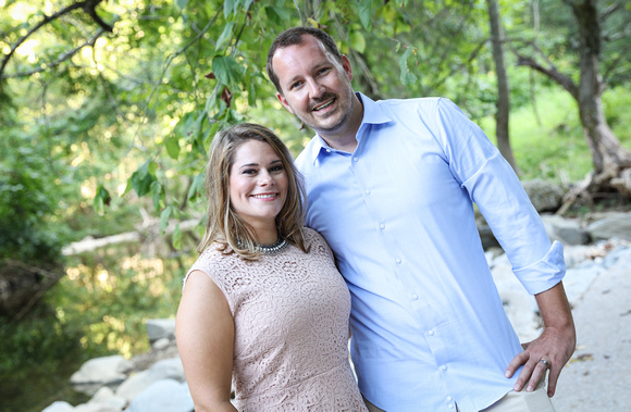 Family photography: a woman in a pink top and a man in blue shirt smile in the woods by a stream.