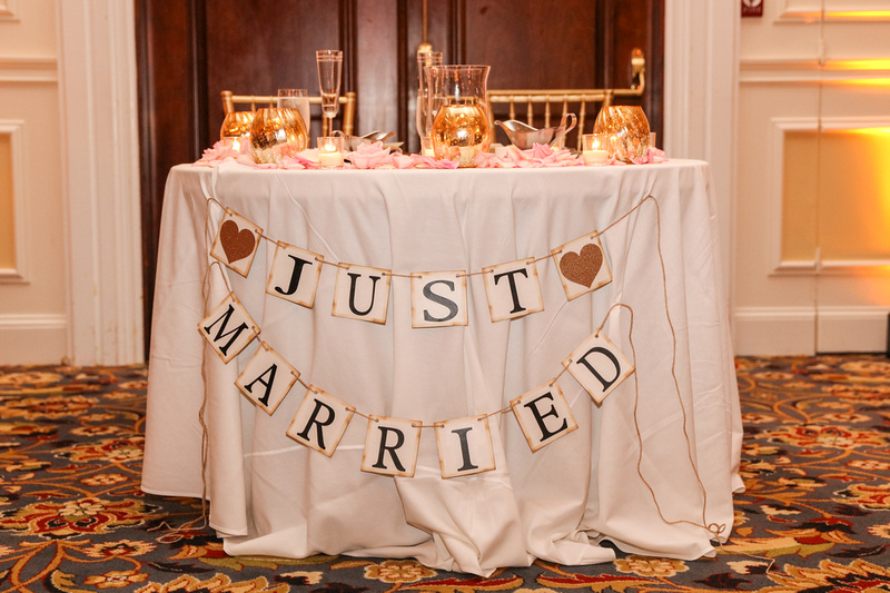 Wedding photography, a sweetheart table with white linen and gold adornments. It says, Just Married.