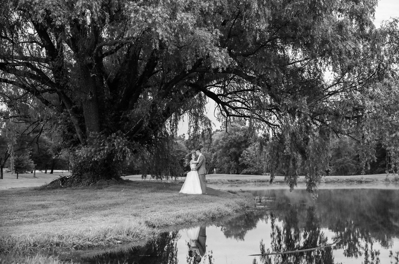 Wedding photography, a bride and groom stand hand in hand, underneath a willow tree by a pond.