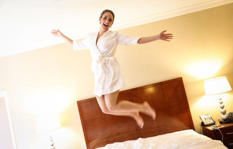 Wedding photography, a beaming bride jumps on her hotel bed with her arms outstretched.