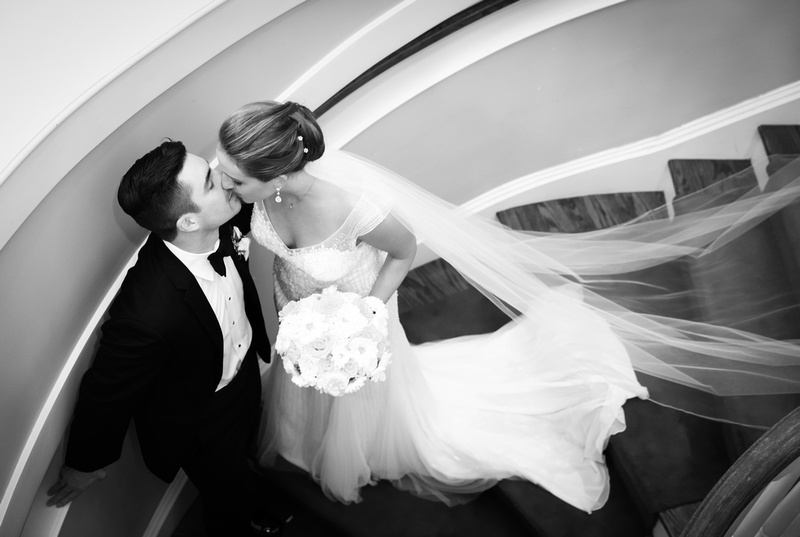 Wedding photography, a bride and groom kiss sweetly on a cascading stairwell. Her veil is draped across the stairs.