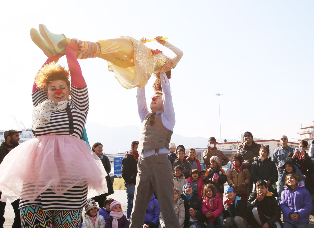 Kolleen in red nose and pink tule clown costume helps hold another clown in the air in front of refugee audience waiting to board the ferry, Lesvos, Greece. 2016 in photos.