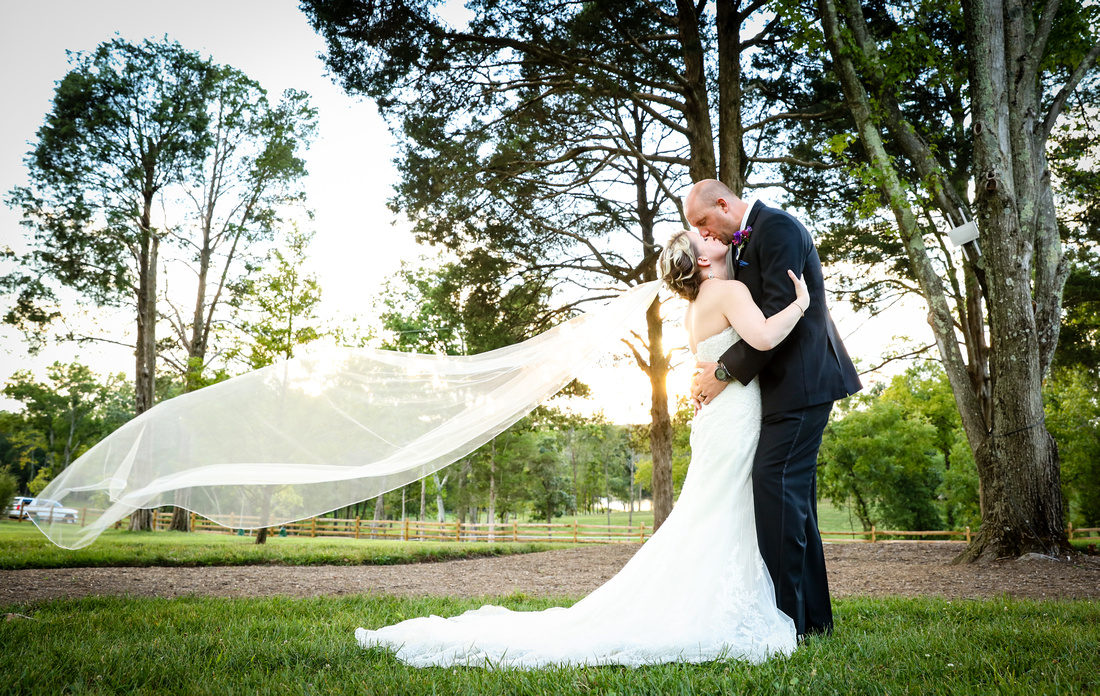 bride and groom embrace in a kiss, long veil floating in the air behind the bride; woodland surroundings. 2016 in photos