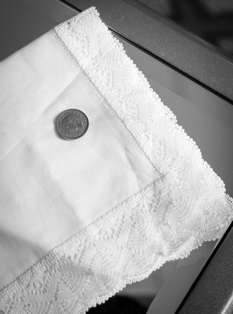 Wedding photography, a two pence piece on a white handkerchief.