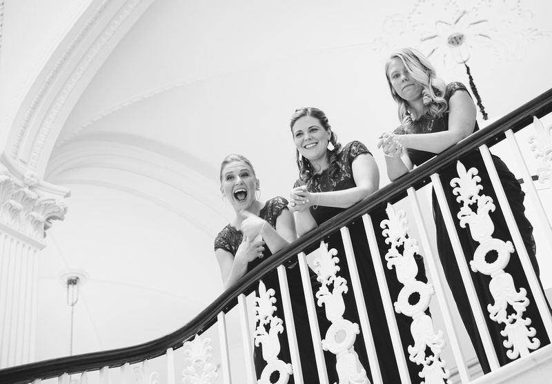 Wedding photography, bridesmaids smile and laugh on a staircase.