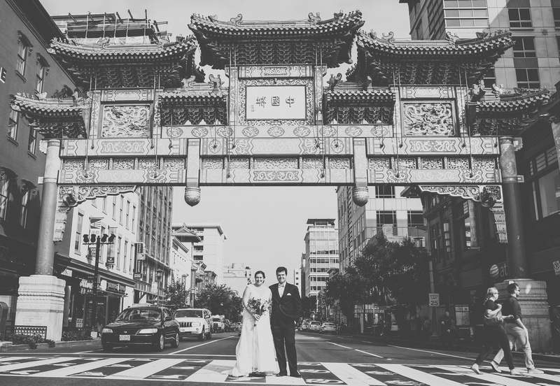 Wedding photography, a bride and groom stand in a crosswalk underneath the Chinatown arch.