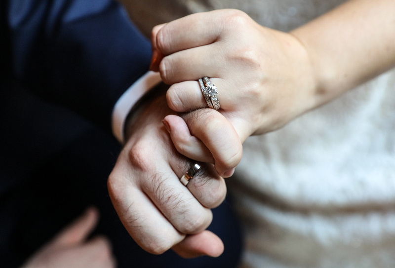 Wedding photography, a closeup of a bride and groom's hands and wedding rings as they link fingers.