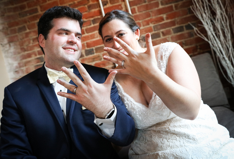 Wedding photography, a bride and groom hold up their hands with wedding rings and smile.