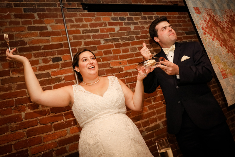 Wedding photography, a bride smiles while holding up her cake fork, the groom gives a thumbs up.