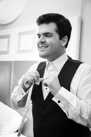 Wedding photography, a groom puts on his bowtie.