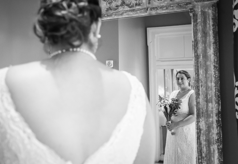 Wedding photography, a bride smiles as she looks at her reflection in the mirror.