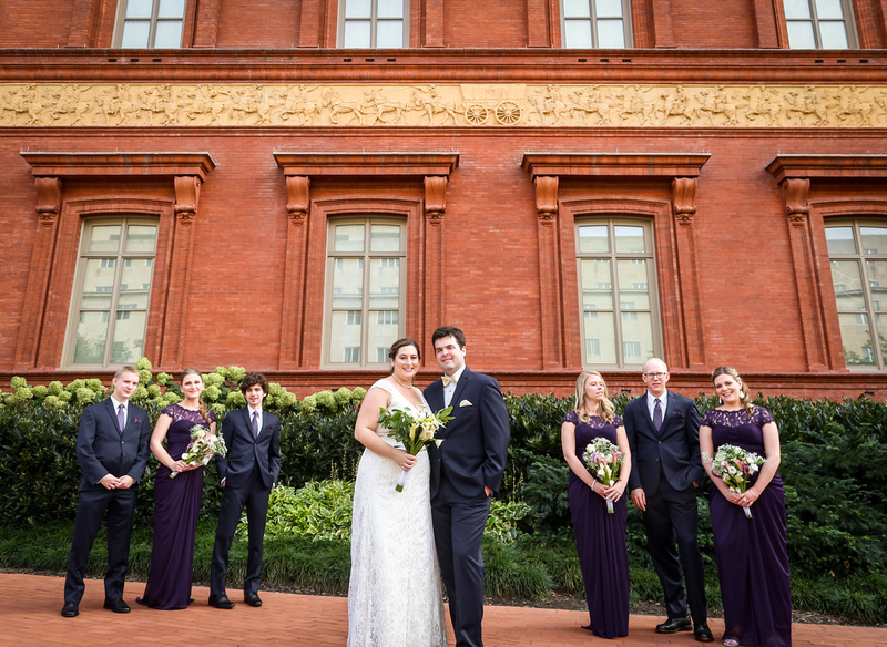 Wedding photography, a wedding party stands in front of a red brick building.
