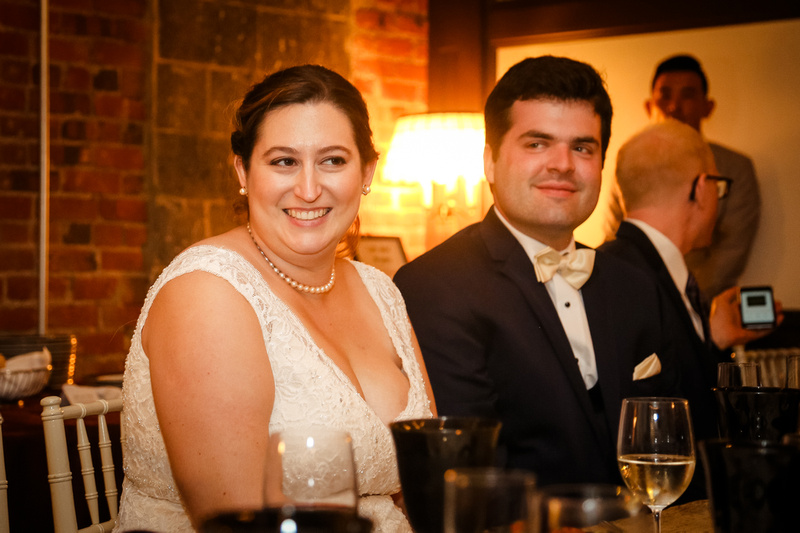 Wedding photography, a bride and groom smile at their dinner table.