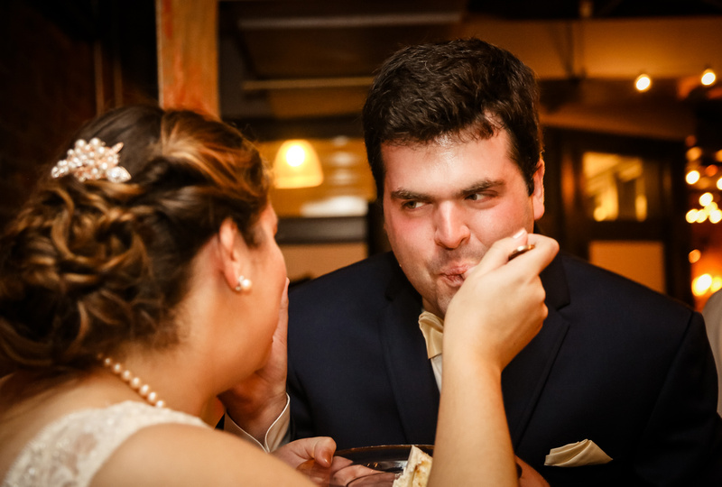 Wedding photography, a bride with pearls in her hair feeds her groom a bite of cake.