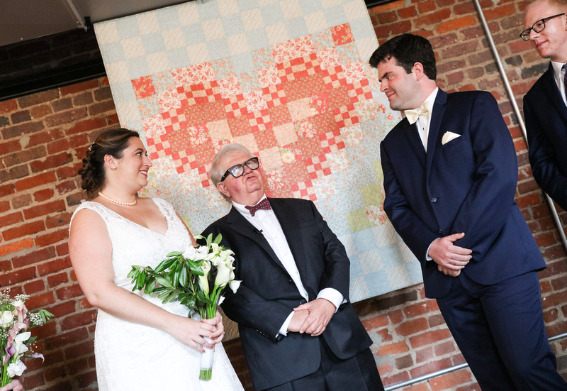 Wedding photography, a bride and groom smile during their wedding ceremony in front of a brick wall.