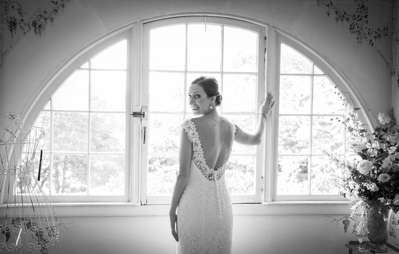 Smiling bride looks behind her and stands in front of large half-dome shaped window. 13 best baltimore wedding venues.