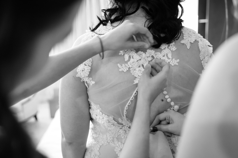 Wedding photography, black and white photo of hands buttoning up the bride's lace wedding dress.