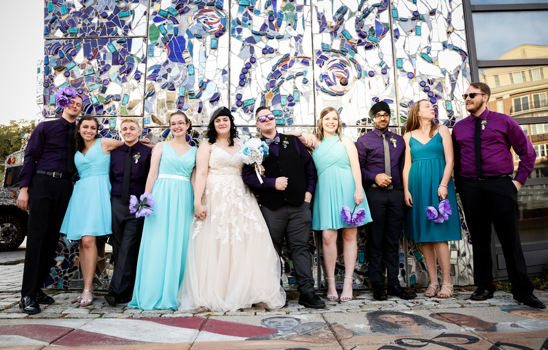 Wedding photography, a bridal party poses in front of a blue stained glass wall.