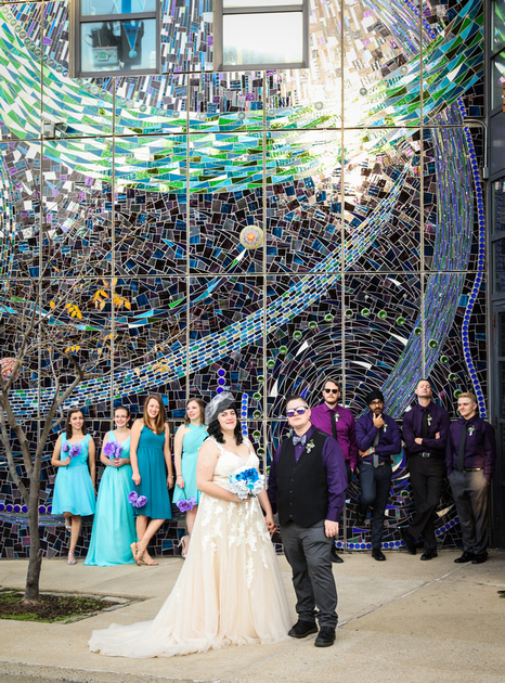Wedding photography, a wedding party poses in front of a blue and green glass building.