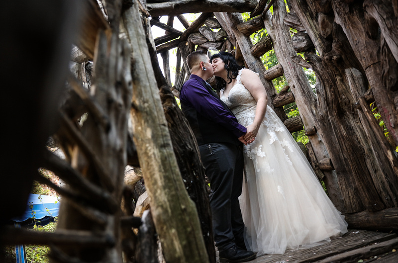 Wedding photography, a bride and groom share a romantic kiss inside a wooden structure.