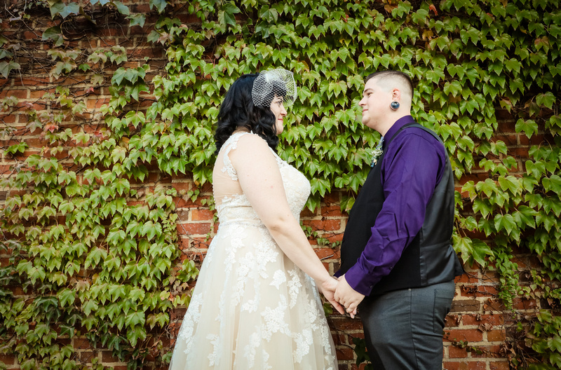Wedding photography, a bride and groom hold hands lovingly in front of a brick wall with green ivy.