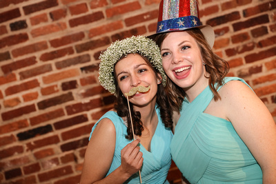 Wedding photography, bridesmaids pose with props at the photo booth.