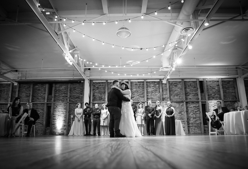 Wedding photography, a black and white image of the first dance. Twinkle lights hang above.