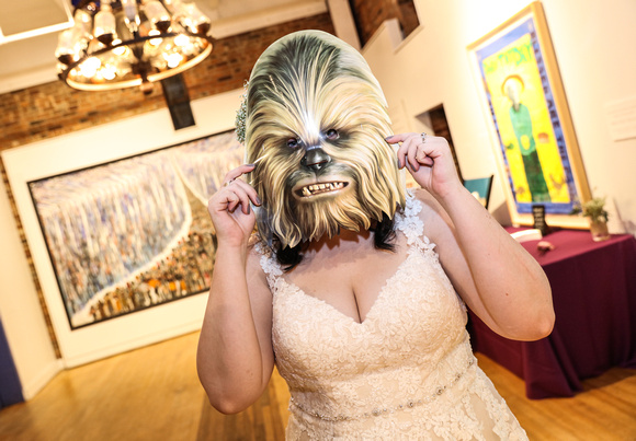 Wedding photography, the bride poses with a Chewbacca mask.