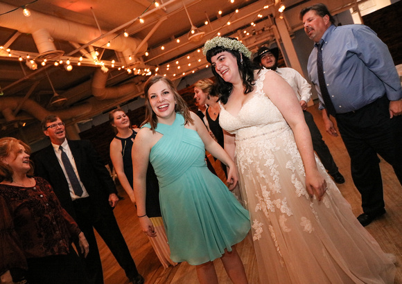 Wedding photography, the maid of honor and bride smile on the dance floor.