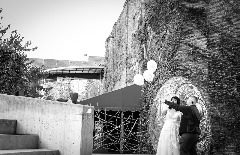 Wedding photography, a black and white image of a bride and groom releasing 3 white balloons.