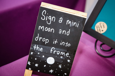 "Wedding photography, a small chalkboard sign says, ""sign a mini moon and drop it into the frame."""