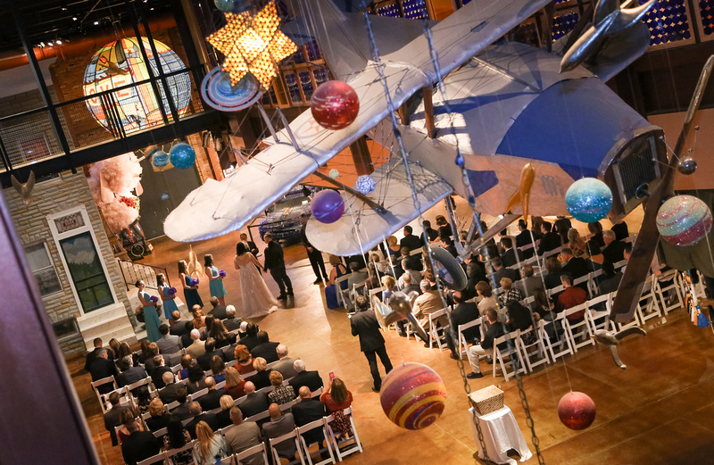 Wedding photography, an overhead shot of a wedding ceremony. There is an airplane and planets hung from the ceiling.