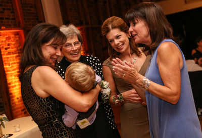 Wedding photography, a group of women crowd around a little baby who is asleep in someone's arms.
