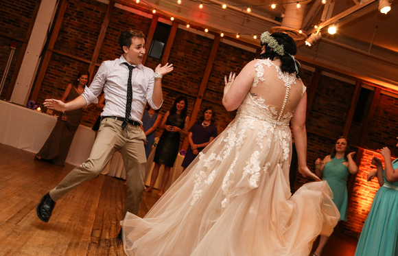 Wedding photography, a wedding guest dances with the bride.