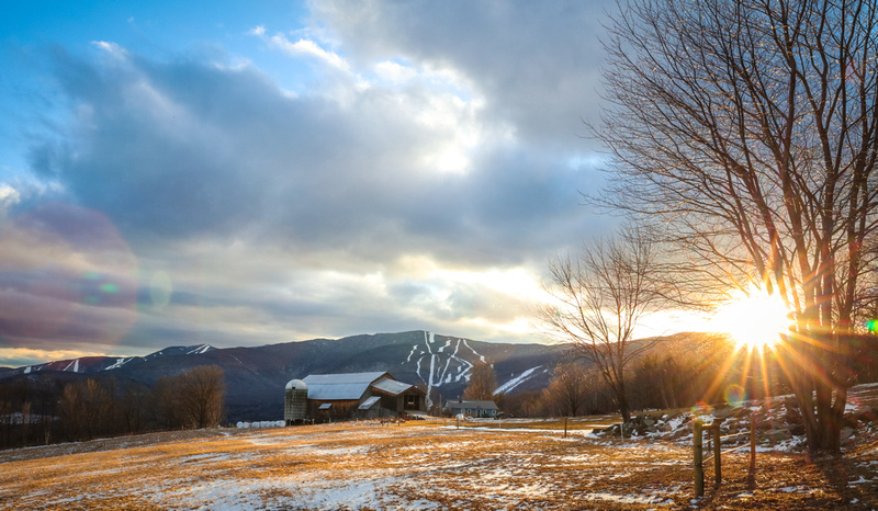 Vermont scenic farm with sun setting behind a mountain