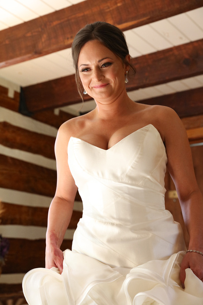 Wedding photography, an emotional bride smiles as she puts on her dress.