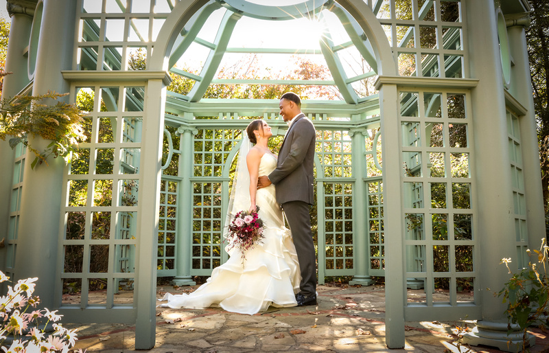 Wedding photography, the sun shining on a bride and groom embracing in a teal gazebo.