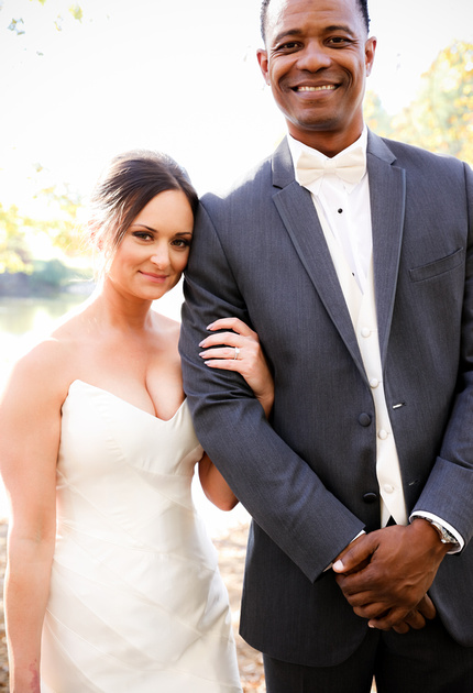 Wedding photography, a small bride and tall groom smile for the camera.