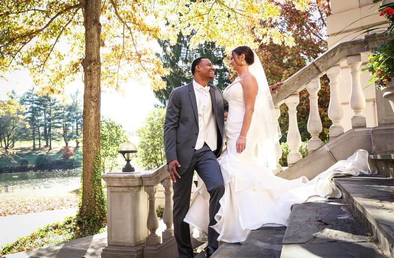 Wedding photography, a bride and groom laugh while standing on a marble staircase with yellow trees behind them.