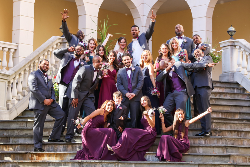 Wedding photography, the bridal party celebrates enthusiastically while standing on a stone staircase.