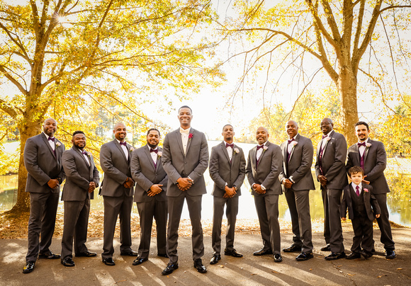 Wedding photography, the groom and groomsmen stand in front of bright yellow trees.