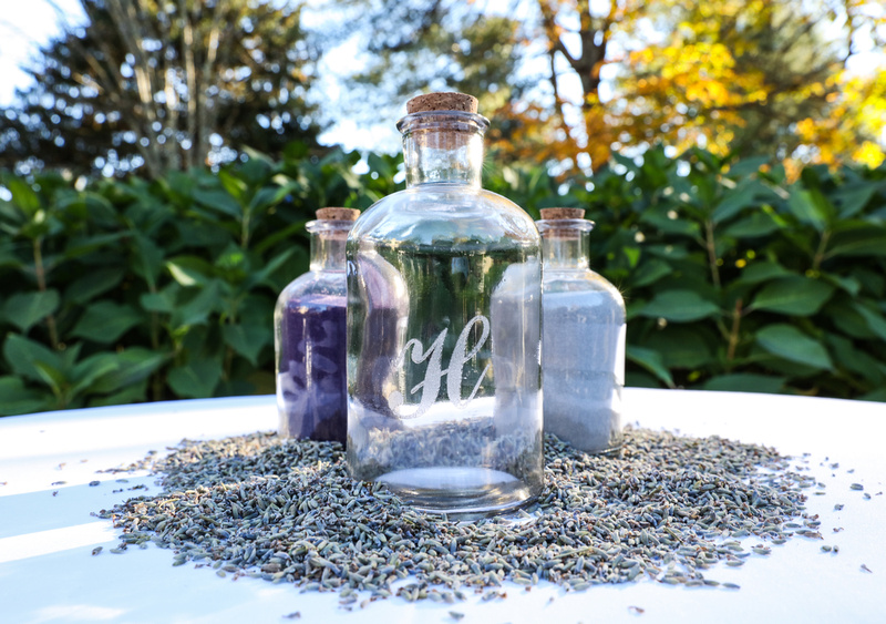 Wedding photography, three glass bottles on a table, two filled with sand, one for lavender seed.