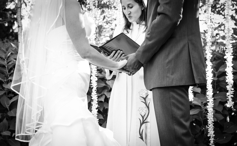 Wedding photography, a black and white close-up image of bride and groom holding hands during the ceremony.