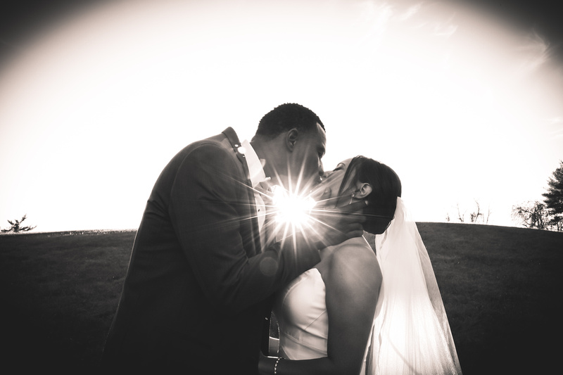 Wedding photography, a black and white image of a bride and groom kissing with a sun spot shining between their bodies.