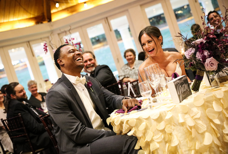 Wedding photography, the bride and groom laugh out loud at their sweetheart table with purple flowers,