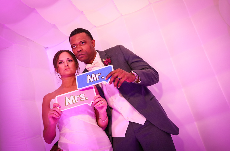 Wedding photography, the bride and groom pose seriously in the purple photo booth.